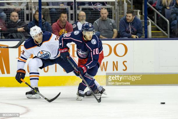 Edmonton Oilers center Leon Draisaitl and Columbus Blue Jackets center Alexander Wennberg battle for the puck during a game between the Columbus Blue...