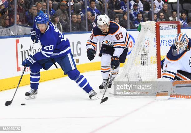 Edmonton Oilers defenseman Matt Benning battles for a puck with Toronto Maple Leafs center Dominic Moore during the third period in a game between...
