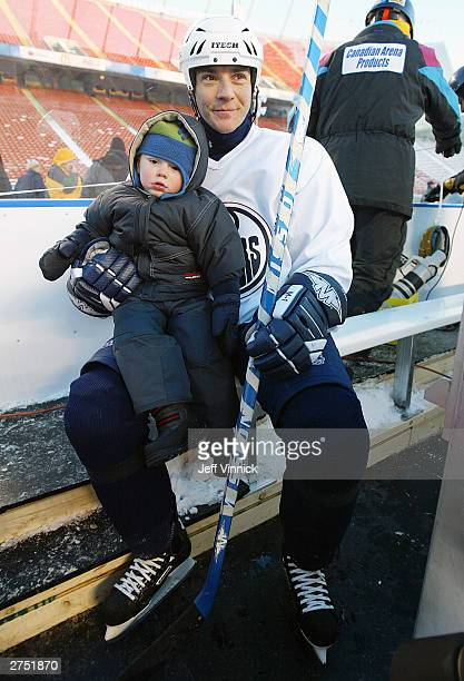 Edmonton Oilers defenseman Steve Staios sits on the team bench with his two yearold son Nathan as they watch the Oilers practice on an outdoor rink...