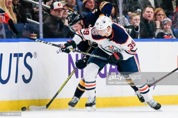 Edmonton Oilers right wing Alex Chiasson and Buffalo Sabres center Jack Eichel fight for puck near boards during the Edmonton Oilers and Buffalo...