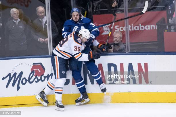 Edmonton Oilers Right Wing Alex Chiasson checks Toronto Maple Leafs Center Auston Matthews into the boards during the second period of the NHL...
