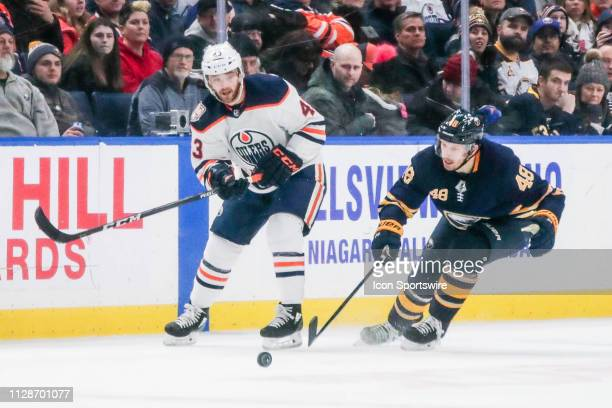Edmonton Oilers right wing Josh Currie and Buffalo Sabres defenseman Matt Hunwick track loose puck during the Edmonton Oilers and Buffalo Sabres NHL...