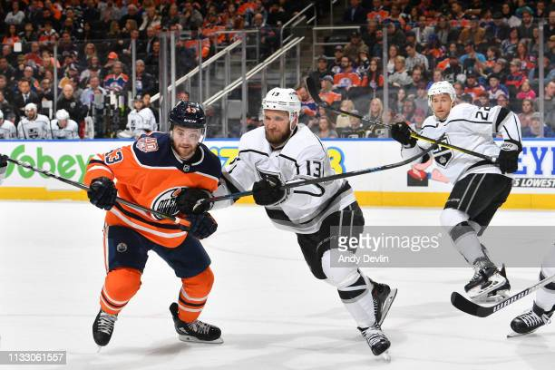 Edmonton Oilers right wing Josh Currie and Los Angeles Kings left wing Kyle Clifford skate to a loose puck on March 26 2019 at Rogers Place in...