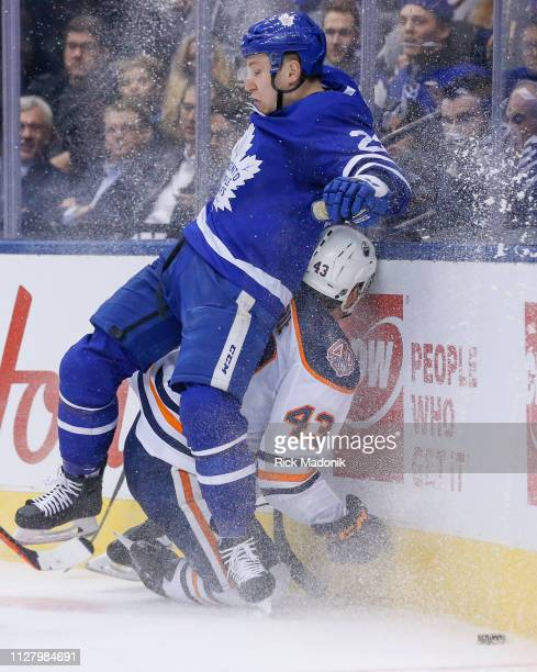 Edmonton Oilers right wing Josh Currie ends up on the losing end of a crunch into the corner with Toronto Maple Leafs defenseman Travis Dermott...