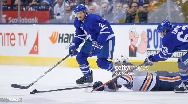 Edmonton Oilers right wing Josh Currie scrambles for a puck as Toronto Maple Leafs left wing Tyler Ennis and Toronto Maple Leafs defenseman Ron...