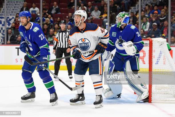 Edmonton Oilers Right Wing Josh Currie stands in front of Vancouver Canucks Goaltender Thatcher Demko as Defenseman Alexander Edler defends during...