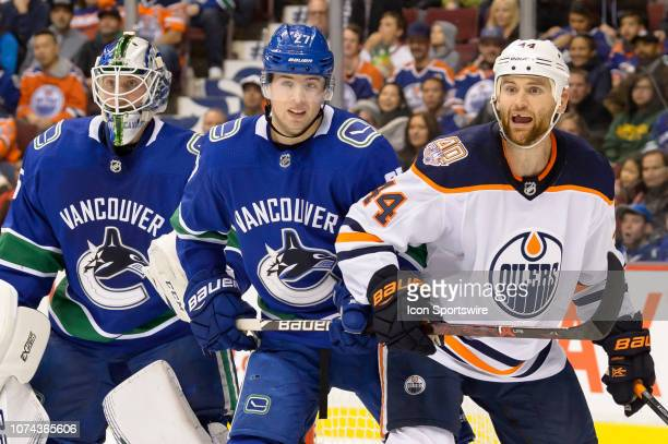 Edmonton Oilers Right Wing Zack Kassian and Vancouver Canucks Defenseman Ben Hutton stand in front of Goaltender Jacob Markstrom during their NHL...