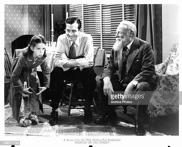 Edmund Gwenn and unknown actor sitting in a chair laughing when a child is making funny gestures in a scene from the film 'Miracle On 34th Street'...