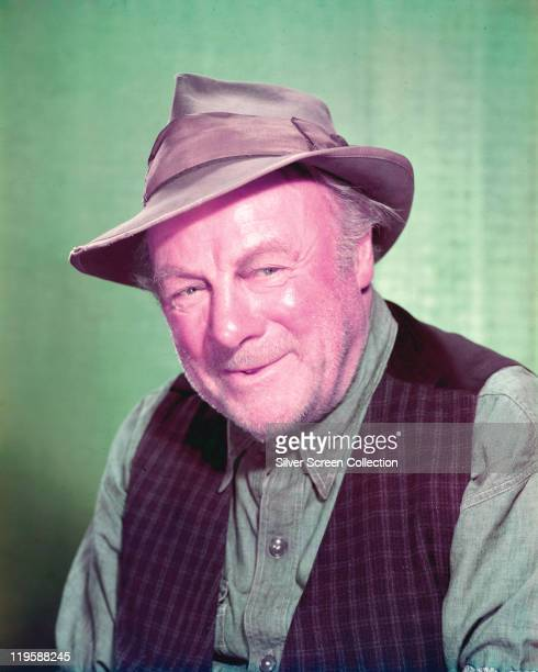 Edmund Gwenn British actor wearing a shortbrimmed leather hat a blue denim shirt and a purple waistcoat in a studio portrait against a pale green...