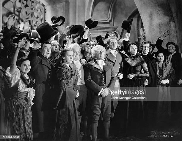 Edmund Gwenn Fredric March and Gale Sondergaard standing in front of a group of people in the 1936 film Anthony Adverse