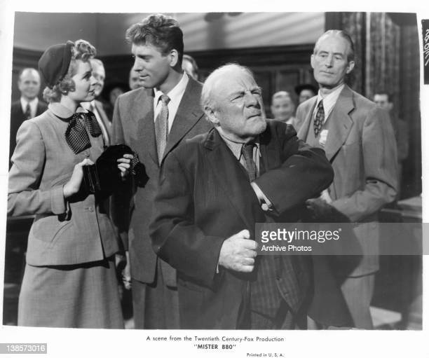 Edmund Gwenn standing with his hand inside his coat in a scene from the film 'Mister 880' 1950