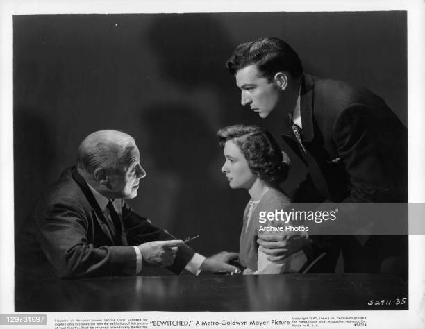 Edmund Gwenn talks to Phyllis Thaxter while Stephen McNally holds her in a scene from the film 'Bewitched' 1945