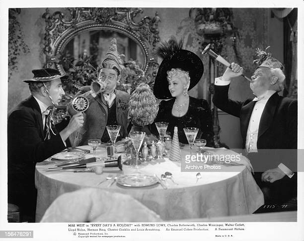 Edmund Lowe and Mae West celebrate with two other men in a scene from the film 'Every Day's A Holiday' 1937
