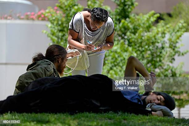 Edna Abraham Gezahegne writes down information about the Denver Rescue Mission to a homeless man in Skyline Park in Denver CO June 16 2014 She said I...