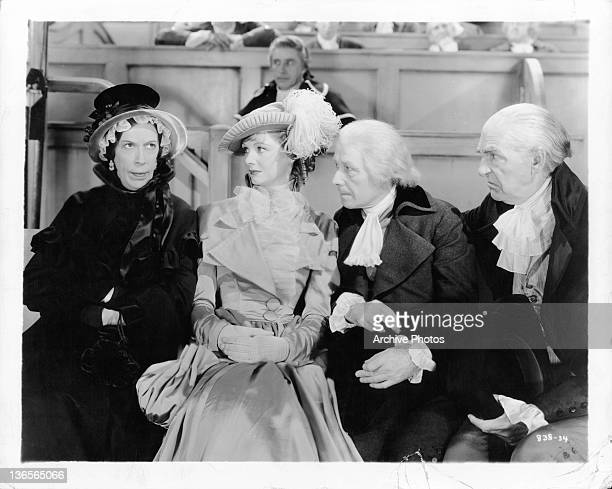 Edna May Oliver with arms folded with Elizabeth Allan Lennox Paule and Ivan Simpson watching in a scene from the film 'David Copperfield' 1935