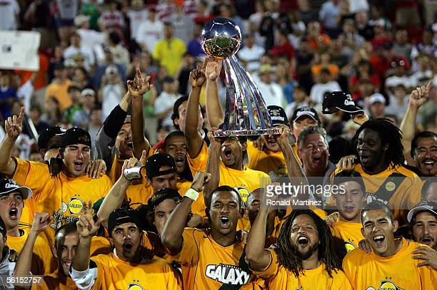 Ednaldo da Conceicao of the Los Angeles Galaxy hoists the Alan I Rothenberg trophy as his teammates celebrate winning MLS Cup 2005 10 in overtime...