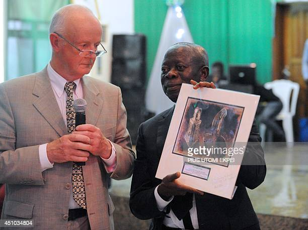 Edo State Governor Adams Oshiomhole holds a catalogue of the Benin bronze artefacts returned by retired hospital consultant Mark Walker during a...