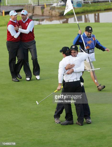 Edoardo Molinari and Francesco Molinari of Europe celebrate holing a putt to halve their match on the 18th green during the Fourball Foursome Matches...