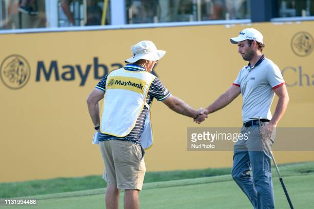 Edoardo Molinari of Italy shakes hand with his caddy on the 18th hole on Day Two of the Maybank Championship at at Saujana Golf and Country Club on...