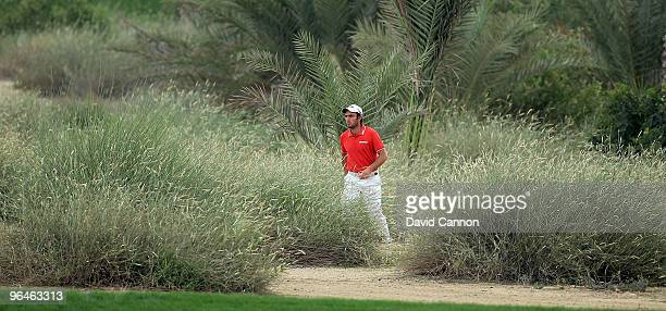 Edoardo Molinari of Italy walks to his second shot at the 16th hole during the third round of the 2010 Omega Dubai Desert Classic on the Majilis...