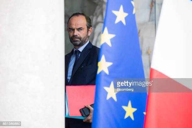 Edouard Philippe France's prime minister passes a European Union flag as departs following a cabinet meeting to approve labor law reforms at the...