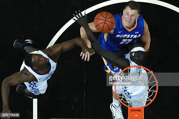 Edrice Adebayo and Wenyen Gabriel of the Kentucky Wildcats fight for a rebound with Rokas Gustys of the Hofstra Pride in the second half of the...