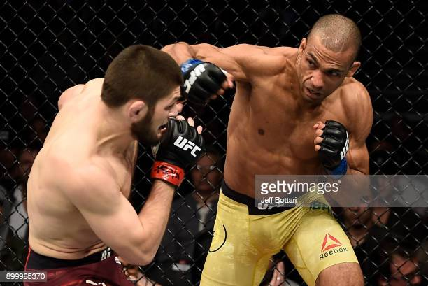 Edson Barboza of Brazil punches Khabib Nurmagomedov of Russia in their lightweight bout during the UFC 219 event inside TMobile Arena on December 30...