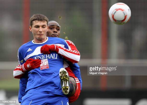 Edson Braafheid of Bayern Muenchen and Mijo Tunjic of Unterhaching fight for the ball during the friendly match between FC Bayern Muenchen and SpVgg...