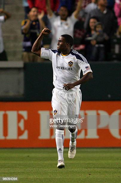 Edson Buddle of the Los Angeles Galaxy gestures to the stands after scoring in the first half during their MLS match against the New England...