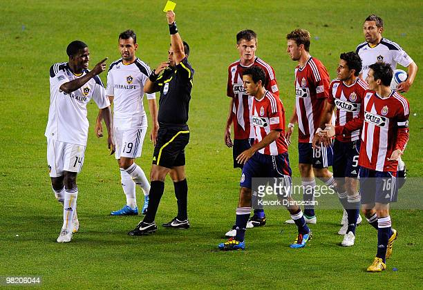 Edson Buddle of the Los Angeles Galaxy is shown the yellow card by referee Ricardo Salazar as he argues with Sacha Kljestan of Chivas USA during the...