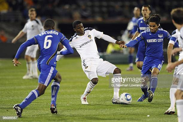 Edson Buddle of the Los Angeles Galaxy looks to make a play with the ball against Pablo Escobar and Stephane Auvray of the Kansas City Wizards during...