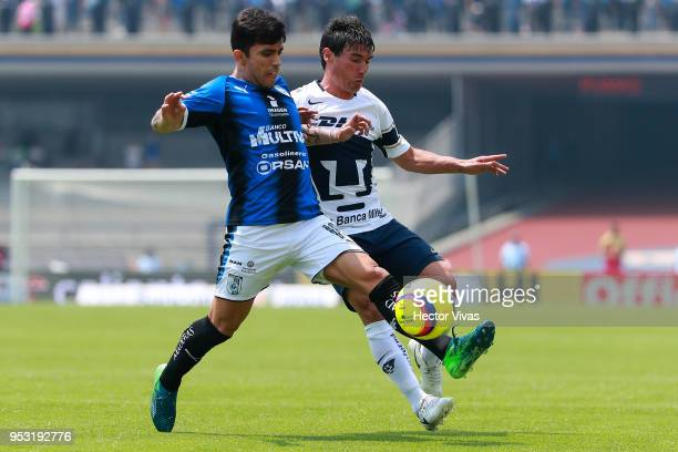 Edson Puch of Queretaro struggles for the ball with Matias Alustiza of Pumas during the 17th round match between Pumas UNAM and Queretaro as part of...