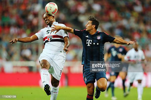Edson Silva of Sao Paulo is challenged by Claudio Pizarro of Muenchen during the Audi Cup match between FC Bayern Muenchen and FC Sao Paulo at...