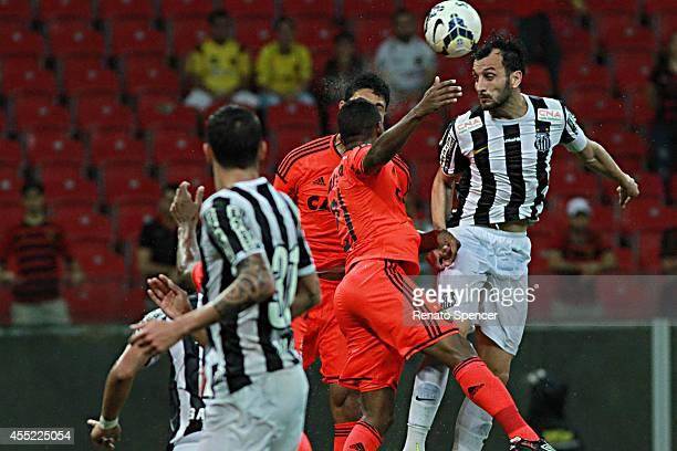 Edu Dracena of Santos wins a header with Ferron and Vitor of Sport Recife during the Brasileirao Series A 2014 match between Sport Recife and Santos...