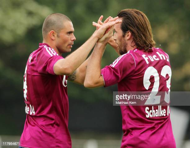 Edu of Schalke celebrates with team mate Christian Fuchs after scoring his team's first goal during the preseason friendly match between Holstein...