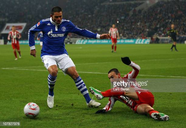 Edu of Schalke challenges Diego Contento of Muenchen during the Bundesliga match between FC Schalke 04 and FC Bayern Muenchen at Veltins Arena on...