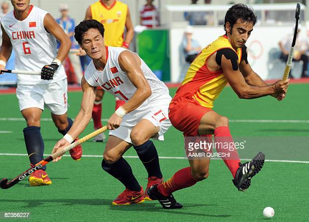 Eduard Arbos of Spain hits the ball as Hu Liang of China defends during their 2008 Beijing Olympic Games men's field hockey match in Beijing on...