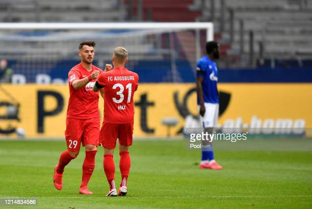 Eduard Loewen of Augsburg celebrates with teammate Philipp Max after scoring their sides first goal during the Bundesliga match between FC Schalke 04...