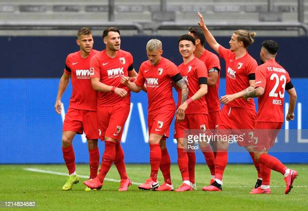 Eduard Loewen of Augsburg celebrates with teammates after scoring their sides first goal during the Bundesliga match between FC Schalke 04 and FC...