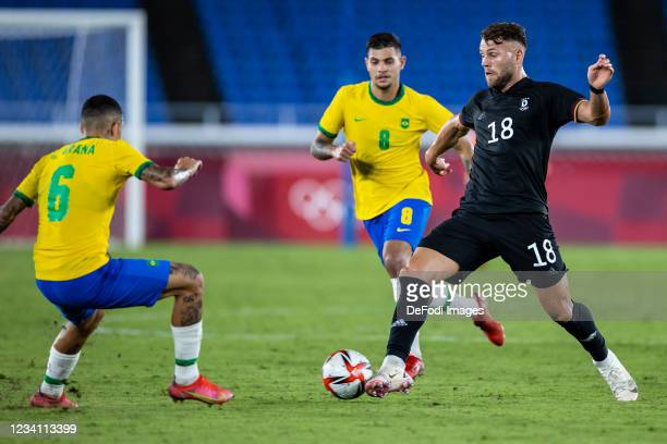 Eduard Löwen of Germany, Guilherme Arana of Brazil and Bruno Guimaraes of Brazil battle for the ball in the Men's First Round Group D match between...