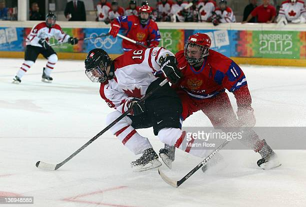 Eduard Nasybullin of Russia and Reid Duke of Canada battle for the puck during the men's preliminary round ice hockey match between Russia and Canada...