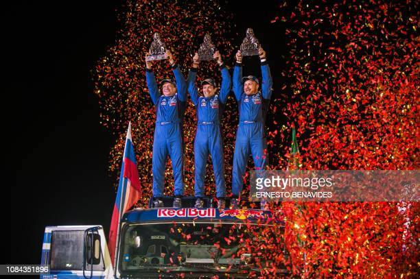 TOPSHOT Eduard Nikolaev Vladimir Rybakov and Evgeny Yakovlev from Russia who took first on their truck celebrate the 2019 Dakar Rally winner's trophy...