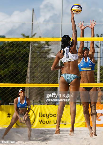 Eduarda Lisboa of Brazil spikes the ball against Rachel Nunes of Brazil during the main draw match at Pajucara beach during day four of the FIVB...
