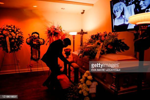 Eduardo Antonio, Cuban singer, and friend of the late Cuban American singer and film actress Rosita Furnes kneels in front of her coffin during the...