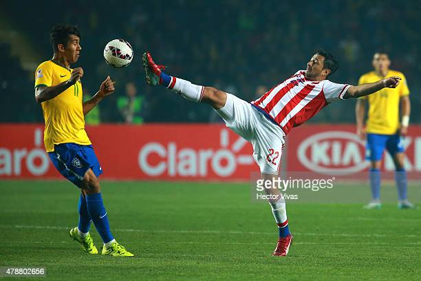 Eduardo Aranda of Paraguay fights for the ball with Roberto Firmino of Brazil during the 2015 Copa America Chile quarter final match between Brazil...