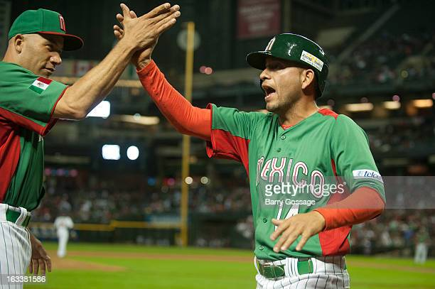 Eduardo Arredondo of Team Mexico is congratulated by teammate Alfredo Aceves after scoring in the top of the first inning of Pool D Game 3 against...