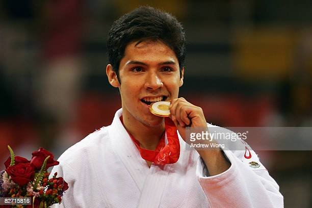 Eduardo Avila of Mexico bites his gold medal after winning the Men's 73 kg Judo contest at Beijing Workers' Gymnasium during day two of the 2008...