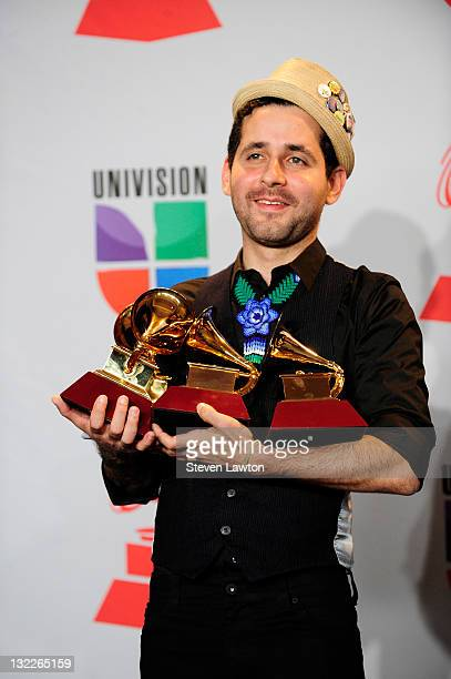 Eduardo Cabra Martinez aka Vistante of the musical group Calle 13 poses in the press room with their multiple Latin Grammy Awards during the 12th...
