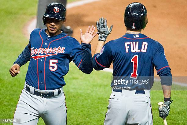 Eduardo Escobar celebrates with Sam Fuld of the Minnesota Twins after Escobar scored during the seventh inning at Progressive Field on May 7 2014 in...