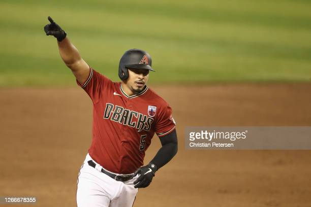 Eduardo Escobar of the Arizona Diamondbacks celebrates as he rounds the bases after hitting a three-run home run against the San Diego Padres during...